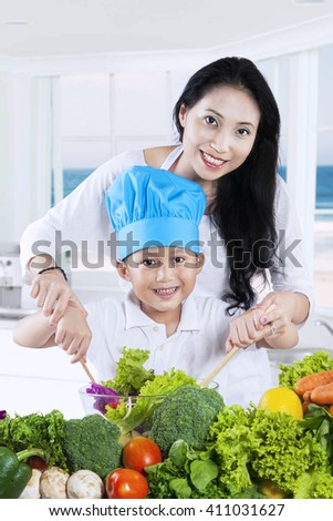 Portrait of beautiful woman and her son cooking vegetables salad in the kitchen while smiling at the camera - stock photo