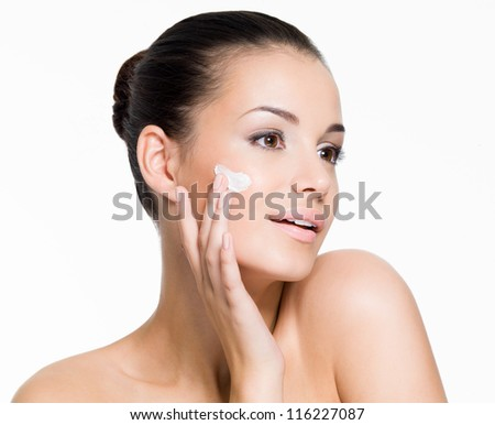 Portrait of beautiful woman applying cream on face - isolated on white - stock photo