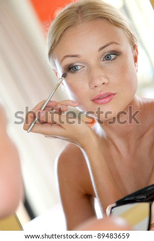 Portrait of beautiful woman applying eyeshadow - stock photo