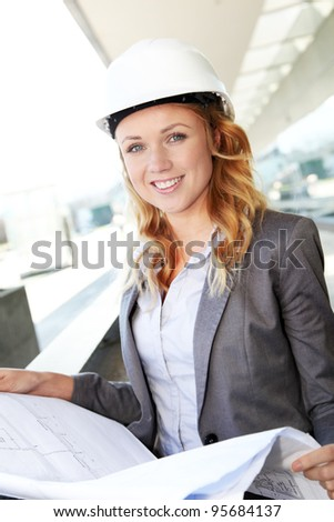 Portrait of beautiful woman architect looking at plan - stock photo