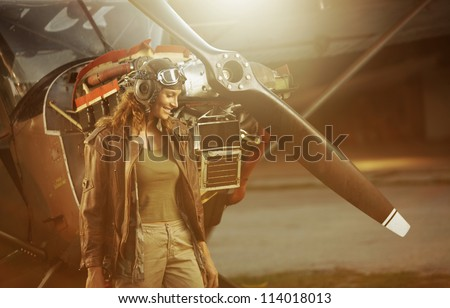 Portrait of beautiful woman aviator in airport at sunset - stock photo
