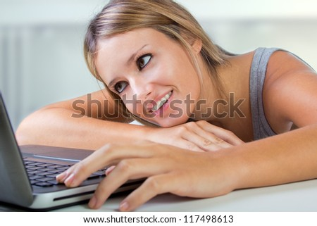 Portrait of beautiful woman browsing internet at home - stock photo