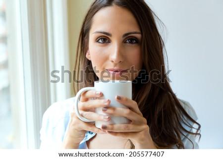 Portrait of beautiful woman drinking coffee in the morning near the window. - stock photo