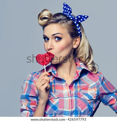Portrait of beautiful woman eating heart shape lollipop. Caucasian blond model posing in retro fashion and vintage concept studio shoot. - stock photo