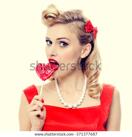Portrait of beautiful woman eating heart shape lollipop, dressed in pin-up style dress in polka dot. Caucasian blond model posing in retro fashion and vintage concept studio shoot. - stock photo