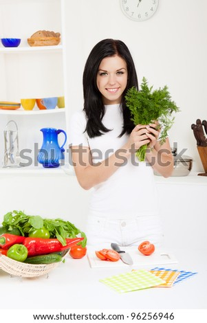 portrait of beautiful woman hold greens in the kitchen, looking at camera happy smile - stock photo