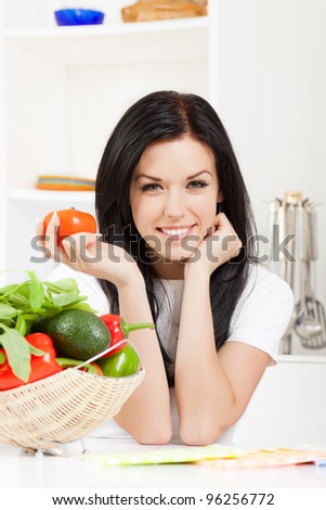 portrait of beautiful woman hold tomato in the kitchen, looking at camera happy smile - stock photo