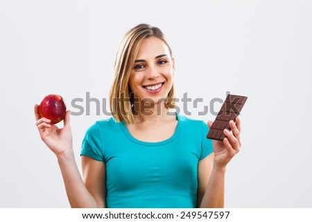 Portrait of beautiful woman holding apple i chocolate.Healthy and unhealthy eating - stock photo