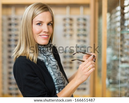 Portrait of beautiful woman holding glasses in optician store - stock photo