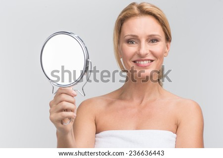 Portrait of beautiful woman holding mirror. smiling woman looking at camera on white - stock photo