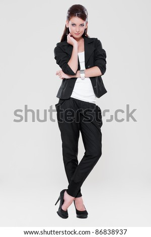 portrait of beautiful woman in black suit over grey background - stock photo
