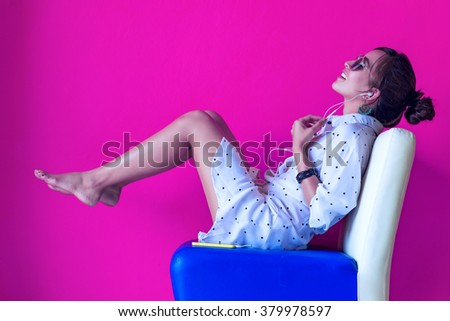 Portrait of beautiful woman in morning listening music sitting on colour sofa at home - stock photo