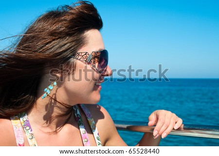 Portrait of beautiful woman in profile on blue sea background. Close up - stock photo