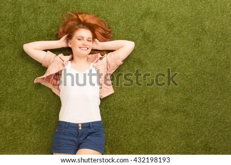 Portrait of beautiful woman in summer clothes lying on green grass and happy smiling for camera. Pretty lady spending her weekends in park. - stock photo