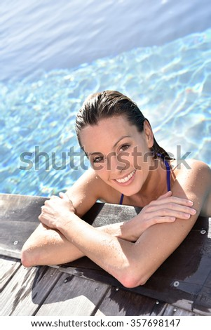 Portrait of beautiful woman in swimming pool - stock photo