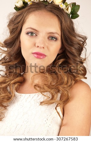 Portrait of beautiful woman in white dress with flower rim - stock photo