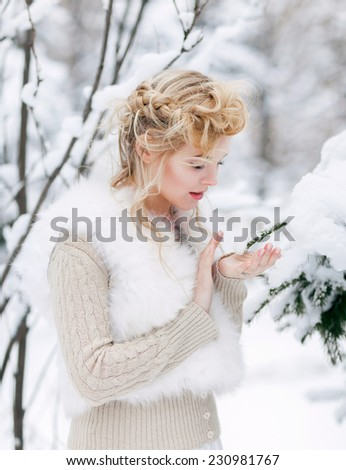 Portrait of beautiful woman in winter forest - stock photo