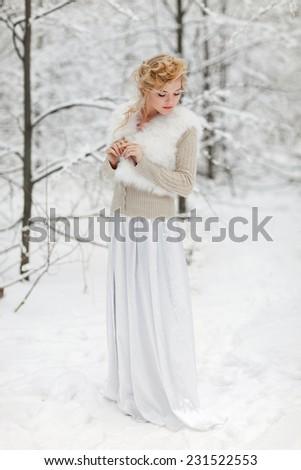 Portrait of beautiful woman in winter park - stock photo