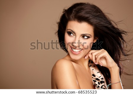 Portrait of beautiful woman isolated on beige looking at copyspace - stock photo