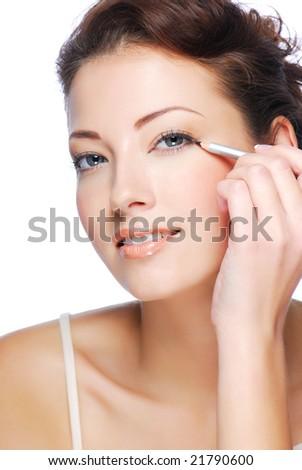 Portrait of beautiful woman making make-up  using black  cosmetic pencil - stock photo