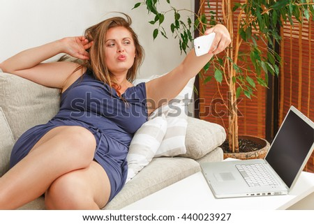 Portrait of beautiful woman making selfie at home. Beautiful lady with red lips looking at camera. Lady lying on sofa or couch. - stock photo