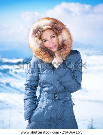 Portrait of beautiful woman on cold weather outdoors, wearing stylish casual blue coat with furry hood, wintertime fashion, winter holidays concept - stock photo