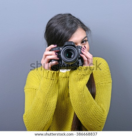 Portrait of beautiful woman photographer holding DLSR camera against gray background - stock photo
