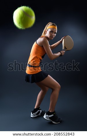 Portrait of beautiful woman playing padel indoor. Isolated on black. - stock photo