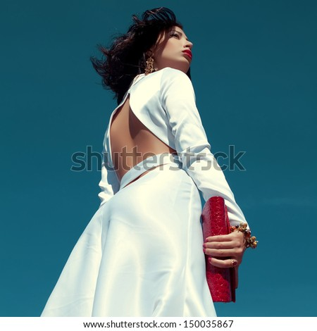 Portrait of beautiful woman posing in elegant white atlas cocktail dress with red leather clutch in her hands over blue sky background. Luxurious golden accessories (bracelet, earrings). Outdoor shot - stock photo