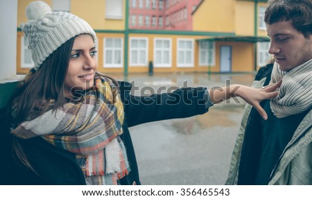 Portrait of beautiful woman rejecting with her hand to young man after a quarrel outdoors. Couple relationships and problems concept. - stock photo