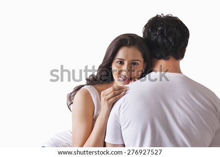 Portrait of beautiful woman resting head on man's shoulder over white background - stock photo