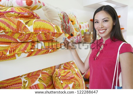 Portrait of beautiful woman shopping cushions in store - stock photo