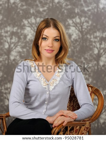 Portrait of beautiful woman sitting on a chair in the modern  interior - stock photo