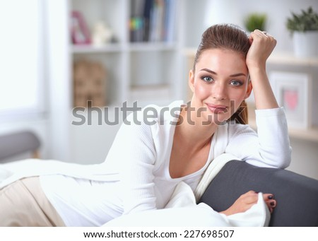 Portrait of beautiful woman sitting on couch at her room - stock photo