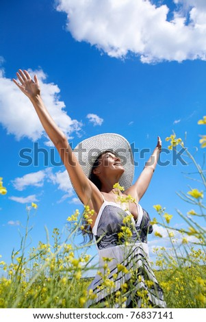 Portrait of beautiful woman standing in the middle of meadow and looking upwards with raised arms - stock photo