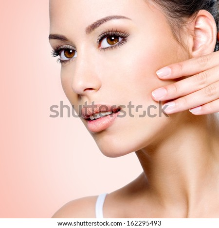 Portrait of beautiful woman touching skin of  face - stock photo