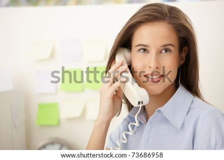 Portrait of beautiful woman using landline phone, smiling in office.? - stock photo