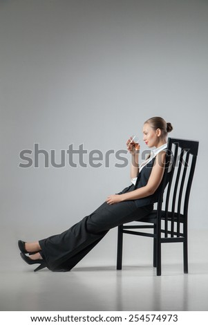 Portrait of beautiful woman wearing black suit sitting on chair herlegs stretched with glass red wine - stock photo