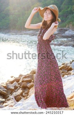portrait of beautiful woman wearing straw hat and long dress standing beside sea beach smiling with happiness emotion use for people relax in vacation destination - stock photo