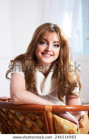 Portrait of beautiful woman with blue eyes  in a  living room - stock photo