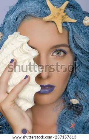 Portrait of beautiful woman with blue hair, shells and open eyes - stock photo