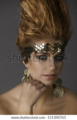 Portrait of beautiful woman with bronze hair shaped like a flame, wearing futuristic fantasy makeup and accessories, holding her hand to her face. - stock photo