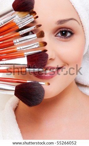 portrait of beautiful woman with brushes for make-up - stock photo