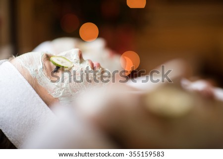 portrait of beautiful woman with cosmetic mask on face in spa and  wellness salon - stock photo