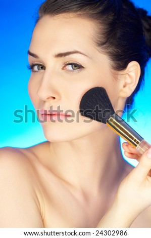 Portrait of beautiful woman with cosmetics brush - stock photo