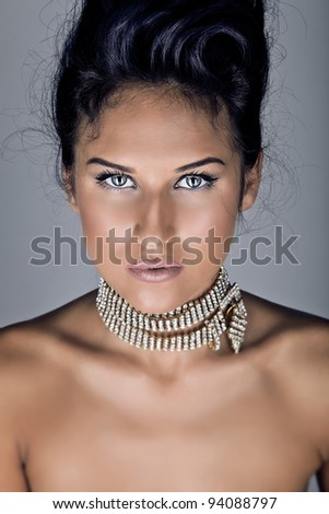 Portrait of beautiful woman with deep blue eyes on grey background - stock photo