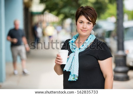 Portrait of beautiful woman with disposable coffee cup on pavement - stock photo
