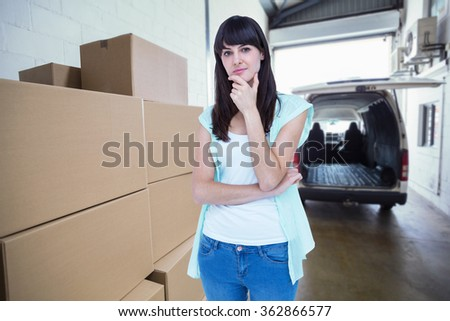 Portrait of beautiful woman with hand on chin against empty van ready to be loaded - stock photo