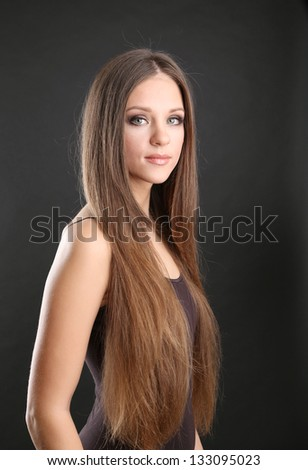 Portrait of beautiful woman with long hair on black background - stock photo