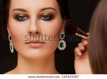 Portrait of beautiful woman with make-up and make-up artist - stock photo